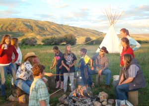 Family roasting marshmallows over a campfire at an American dude ranch in Colorado