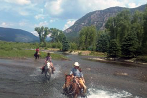 Three adults on horseback riding through a river on an American dude ranch vacation