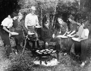 Vintage black-and-white photo of a family cooking pancakes over a campfire at a Colorado dude ranch